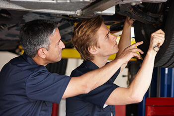Young adult male being trained on auto mechanic skills